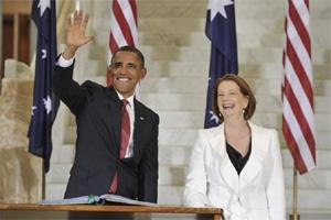 US President Barack Obama, left, waves after signing the visitor's book as Julia Gillard, Australia's prime minister, looks on at Parliament House in Canberra, Australia, on Wednesday. Obama and Gilla
