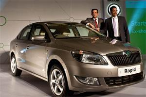 Head marketing Skoda India Tarun Jha (R) and associate director sales Ashutosh Dixit (L) pose with the newly unveiled Skoda Rapid in New Delhi. Manan Vatsyayana/AFP