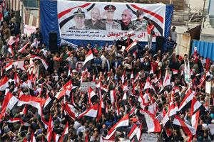 Egyptian supporters of Egypt's ruling military council hold up a banner showing some of the council members. Photo: AP