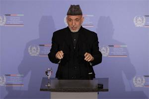 Afghanistan's President Hamid Karzai addresses the delegates during a dinner one day ahead of the Afghanistan conference to be held in Bonn , Sunday. AP