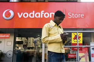 A pedestrian using a mobile phone stops outside a Vodafone store in Mumbai. Photo: Bloomberg