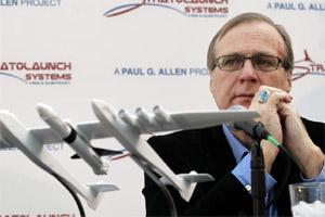 Microsoft co-founder Paul Allen looks across at a model of a giant airplane and spaceship he plans on building, during a news conference about the plane on 13 December 2011, in Seattle. AP