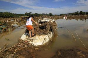 A woman inspects a submerged vehicle in a village hit by flashfloods brought by Typhoon Washi in Cagayan de Oro. Photo: Reuters