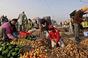 Customers rummage through heaps of vegetables at a market in Amritsar. AP