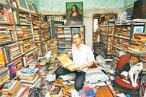 Man of words: Shashikant Sawant lives with his dog, Mozart, in a room crammed with books and watched over by a Mona Lisa print. (Photo Hemant Mishra/Mint)
