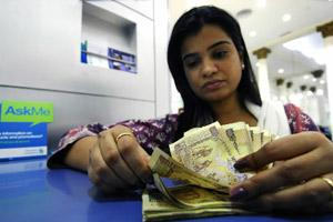 A woman counts Rs500 notes at a Standard Chartered Bank branch in Mumbai. Bloomberg