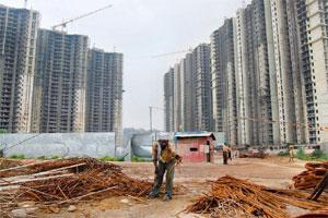 Financial strain: A residential project under construction in Gurgaon. The IDFC report says real estate firms may be forced to slash prices by 10-25% due to poor sales. Mint