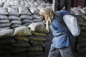 Laborer unloads cement bags from freight trains. Photo: Bloomberg