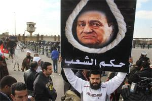 "A man holds a placard depicting ousted President Hosni Mubarak with Arabic writing that reads, ""trial of the people,"" in front of a courtroom in Cairo on Wednesday. AP"