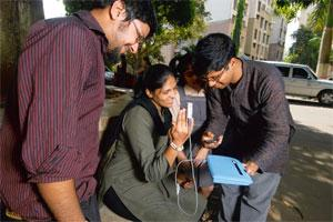 Doorstep service: Abhishek Sen (extreme left) and Myshkin Ingawale test a woman's haemoglobin count in Thane, Mumbai.