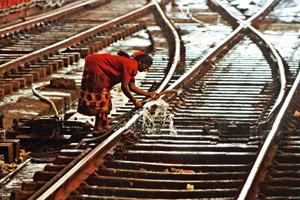 Clean-up: A file photo of a worker cleaning railway tracks. Rail corrosion due to human waste costs the railways more than Rs350 crore every year, the railway minister said.