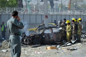 Afghan firefighters distinguish a burning vehicle in front of a guesthouse in Kabul on Wednesday, after a suicide bomb attack. Taliban insurgents claimed a suicide attack in the Afghan capital Kabul,