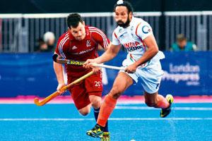Feeling blue: Britain's James Tindall (left) and India's Sardar Singh. Photo by Sang Tan/AP.