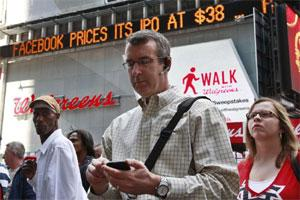People gather outside the NASDAQ Marketsite waiting to see Facebook's share prices posted inside on video monitors in New York on 18 May 2012. Reuters