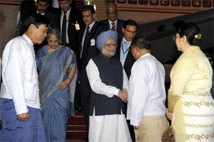 Prime Minister Manmohan Singh (C) shakes hands with Myanmar's foreign minister Wunna Maung Lwin upon his arrival at the airport in Naypyitaw. Photo: Reuters.