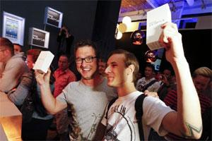 Customers pose for the media after they were first in line to buy Samsung Electronics' new Samsung Galaxy SIII smartphones during a late night sale event in Berlin. Photo: Reuters