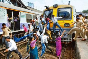Disrupting transport: Police try to disperse protestors attempting to stop a train at Malad railway station in Mumbai on Thursday.(Santosh Hirlekar/PTI)