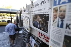 Newspapers with front page stories about the results of the Greek elections hang from a display stand outside a street kiosk in Athens, Greece, on Monday. Bloomberg
