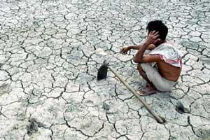 A farmer waits for rain on his drought hit paddy field (AFP)