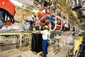Reaching out: Workers at Maruti Suzuki plant in Manesar in Haryana. The firm has been in talks with the Haryana government to acquire as much as 50 acres of land. Photo: Ramesh Pathania/Mint
