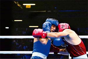 Knocked out: Abbos Atoev of Uzbekistan (in red) during his win over Vijender Singh of India in the middle-weight boxing quarterfinals on Monday. Photo: Jack Guez/AFP