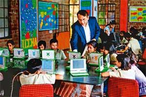 One for all: Students at the Katha school in Delhi's Govind puri slum cluster learn using low-cost OLPC XO laptops, with Jha. (Pradeep Gaur/Mint)