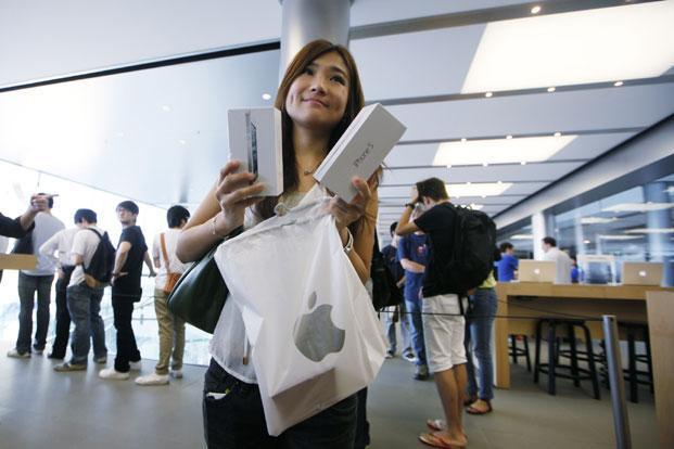 A customer shows her new iPhone 5 at the Apple store in Hong Kong on Friday. Apple's Asian fans jammed the tech juggernaut's shops in Australia, Hong Kong, Japan and Singapore to pick up the latest version of its iPhone. Photo: Kin Cheung/AP