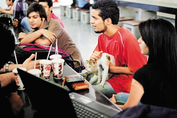 Student Faizan Ashraf Dar (centre) with Adrian the cat. Photo: Pradeep Gaur/Mint