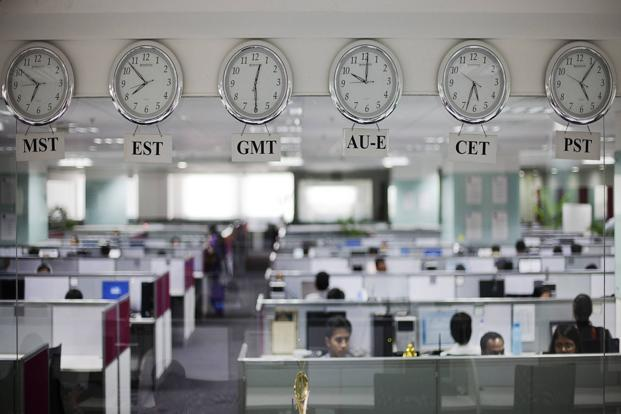 Workers are pictured beneath clocks displaying time zones in various parts of the world at an outsourcing centre in Bangalore. Photo: Vivek Prakash/Reuters