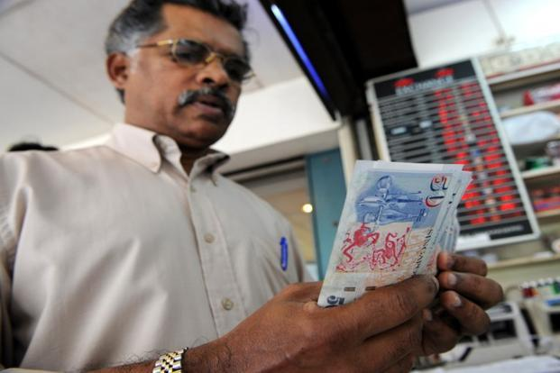A dealer counts Singapore dollar notes at a money changer in Singapore. In the last two months, three companies—IDBI Bank Ltd, Exim Bank Ltd and Indian Oil Corp. Ltd (IOC) have raised a total of around S$900 million. Photo: AFP (AFP)