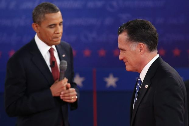 Republican presidential candidate Mitt Romney (right) and US President Barack Obama walk past each other during a town hall style debate at Hofstra University in Hempstead, New York. Photo: Getty Images/AFP