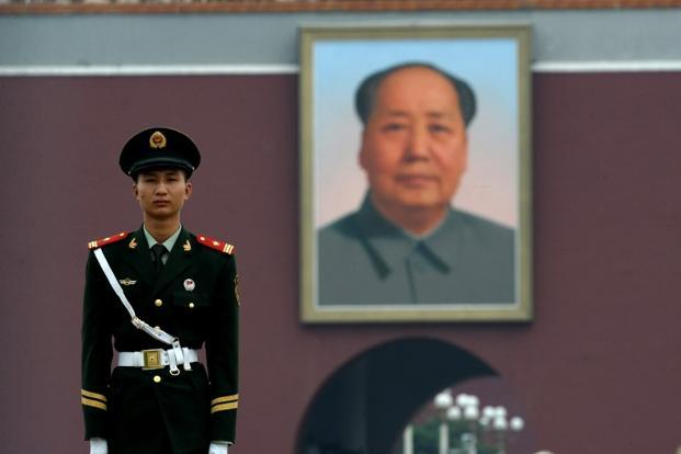 A Chinese paramilitary policeman stands guard in front of a huge portrait of the late Chinese leader Mao Zedong at Tiananmen Gate in Beijing. Photo: Nicolas Asfouri/AFP