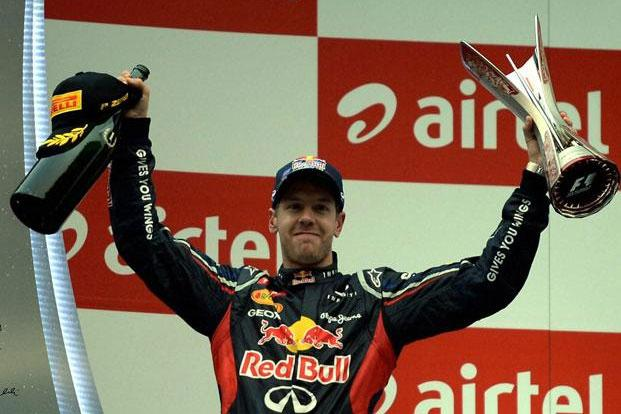 Red Bull's Sebastian Vettel of Germany celebrates with champagne and trophy after winning the Indian Formula One Grand Prix at the Buddh International Circuit in Greater Noida on Sunday. Photo: PTI