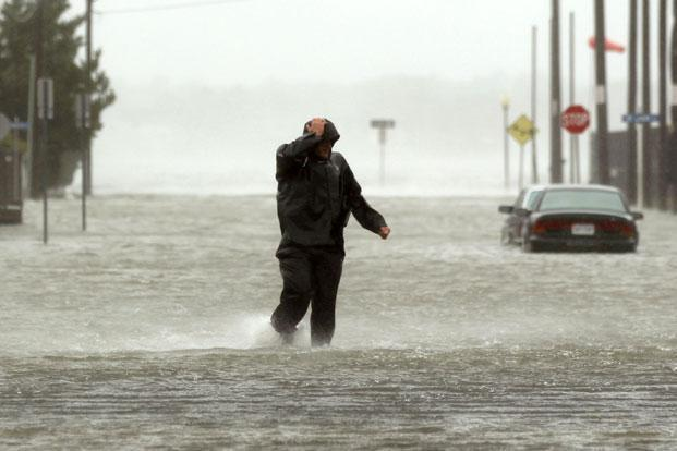 Bracing against the wind, a man wades through a street flooded during Hurricane Sandy in Ocean City on Monday. Photo: Kevin Lamarque/Reuters