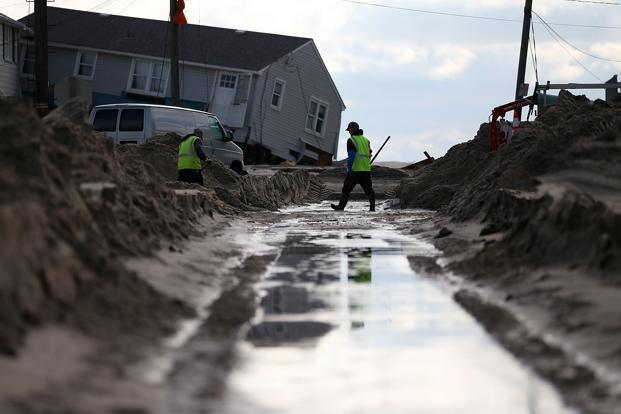 City workers turn off a water main on a street filled with sand from Hurricane Sandy in Long Beach Island, New Jersey. Photo: Mark Wilson/AFP