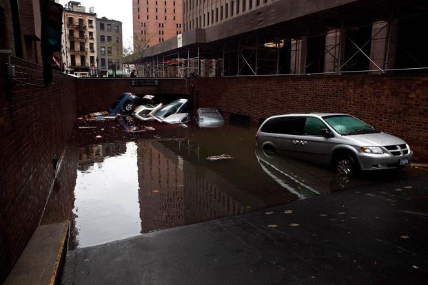 Cars floating in a flooded subterranian basement following Hurricaine Sandy in the Financial District of New York. Andrew Burton/Getty Images/AFP