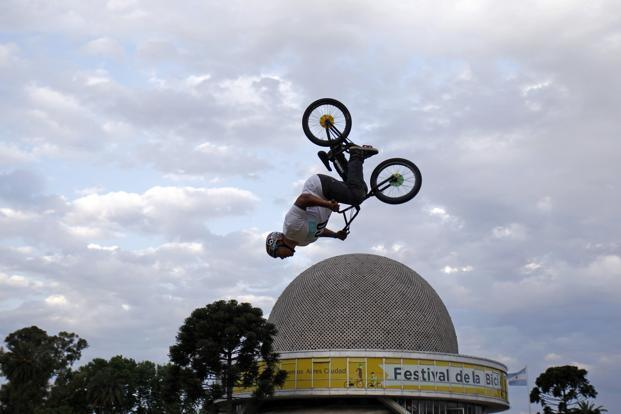 A man performs a trick on a bicycle during a Bicycle Festival outside Buenos Aires' planetarium, Argentina. Reuters