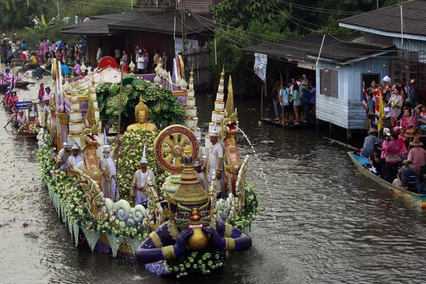 People throw lotus flowers from a decorated boat carrying a Buddha statue during the Lotus Flower Receiving Festival in Bangkok. The festival is held annually to celebrate the end of Buddhist Lent and the rainy season. AP