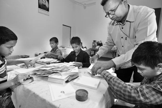 Visually-challenged children who live at the Blind Relief Association hostel help to block-print paper that is used to make cards