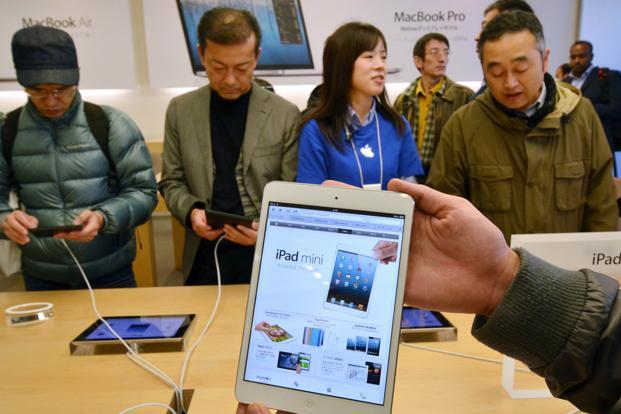 Customers try out the newly launched 7-inch sized tablet 'iPad mini' at an Apple store in Tokyo on Friday. Photo: AFP