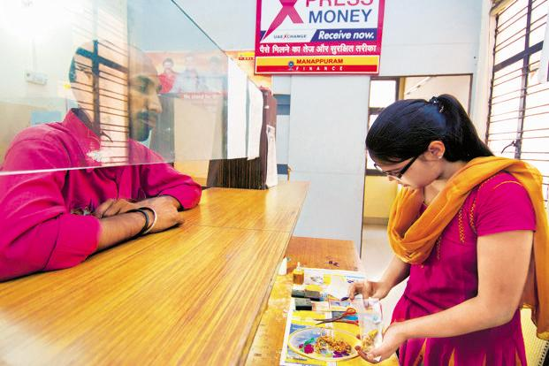 A Manappuram Finance staffer checks gold ornaments before evaluating them for a loan. Photo: Ramesh Pathania/Mint (Ramesh Pathania/Mint)