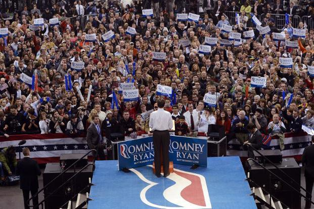 Supporters carry placards and cheer for Romney during his last campaign rally in Manchester. AFP