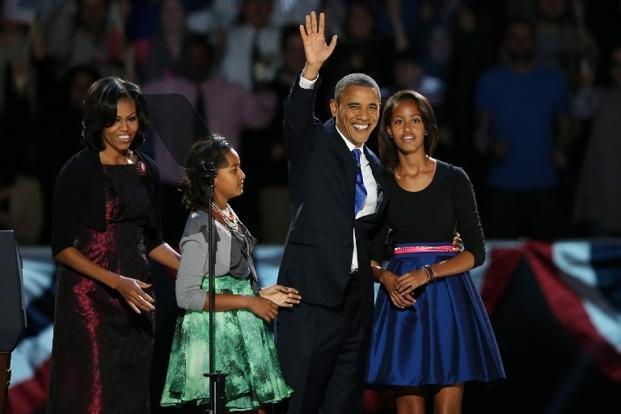 US President Barack Obama walks on stage with first lady Michelle and daughters Sasha and Malia to deliver his victory speech on election night at McCormick Place in Chicago, Illinois. AFP