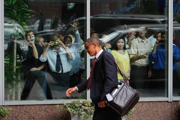 19 August 2008: People watch as presumptive US Democratic presidential nominee Senator Barack Obama arrives at the Sheraton hotel on in Raleigh North Carolina. AFP