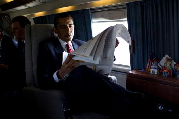22 May 2009: A voracious reader that he is; Obama reads the business section of the New York Times while flying to the US Naval Academy aboard the Marine One helicopter. Official White House Photo.