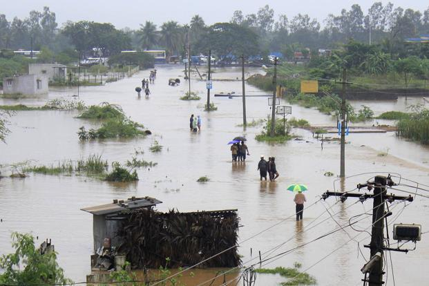 Residents wade through flood waters in Visakhapatnam in Andhra Pradesh on Monday. Downpours triggered by a cyclone last week have left hundreds of villages inundated and nearly 70,000 people in relief camps. Photo: AFP