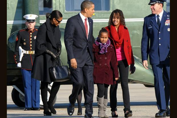24 December 2009: Obama, first lady Michelle (left) and their daughters Malia(right) and Sasha arrive to board the Air Force One at the Andrews Air Force Base in Maryland on to leave for Hawaii for Christmas vacation. AFP