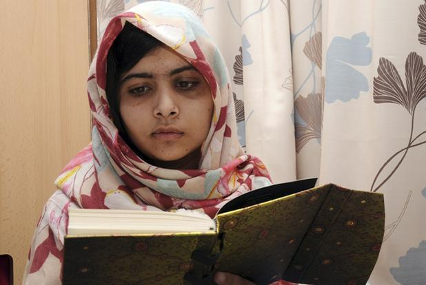 On Friday, the hospital where Malala is being treated released photographs of her reading a book and clutching a white teddy bear, dark bruises covering her eyelids. Photo: AP/Queen Elizabeth Hospital
