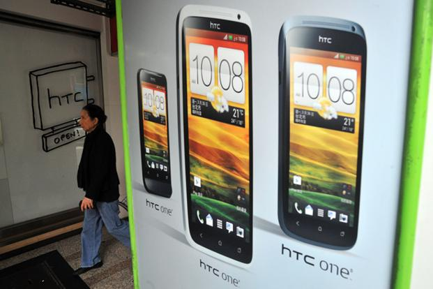 A woman walks past a HTC store in the Younghe district of New Taipei City. Photo: AFP