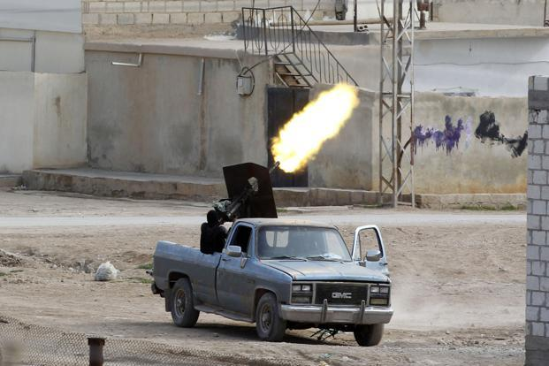 A Free Syrian Army fighter fires an anti-aircraft artillery weapon during an air strike in the Syrian town of Ras al-Ain, as seen from the Turkish border town of Ceylanpinar on Tuesday. Photo: Osman Orsal/Reuters